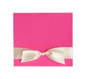 Розовая карточка с бежевым смычком на белой предпосылке Стоковая Фотография