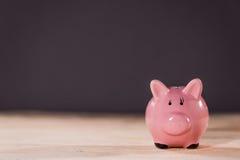 Розовая керамическая копилка на верхней части деревянного стола, концепции сбережений копилки Стоковое Изображение RF