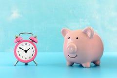 Розовая копилка свиньи на голубой предпосылке Рядом малый розовый холодильник Стоковые Фото