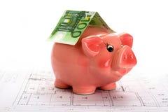 Розовая копилка с банкнотой евро на изолированном чертеже дома, верхнем стоковое фото rf