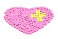Розовая пилюлька сформированное сердце и желтые пилюльки помещены в перекрестной форме Творческая концепция здравоохранения и мед Стоковая Фотография RF