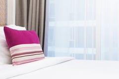 Розовая подушка нашивки на белой кровати в ярко освещенной спальне стоковое фото