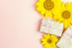 Розовая предпосылка с желтыми солнцецветами и подарочной коробкой стоковая фотография rf