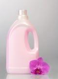 Розовая пластичная бутылка с жидкостным тензидом, цветком орхидеи на сером цвете Стоковые Фотографии RF