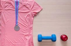 розовая рубашка, красные яблоки, спорт, одежда, взгляд сверху, медаль, dumbb Стоковые Фото