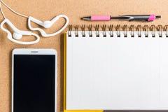 Розовая ручка с желтой тетрадью и чернь с белым наушником o Стоковые Изображения