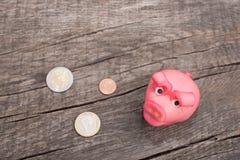 Розовая свинья марципана с монетками на древесине Стоковые Фотографии RF