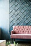 Розовая софа на голубой предпосылке стены, месте для надписи стоковое изображение