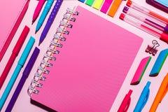 Розовая тетрадь рядом с яркими ручками стоковые изображения