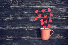 Розовая чашка на деревянной старой предпосылке с красными сердцами Валентайн дня s Фото с тонизировать Стоковое Изображение RF