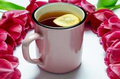 Розовая чашка чаю со стойками лимона на белой предпосылке рядом с розовыми тюльпанами стоковая фотография rf