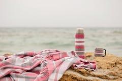Розовая шотландка в клетке и thermos с чашкой на камне на Стоковое Фото