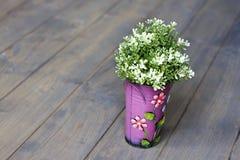 Розовое ведро с florets искусственное зеленое растение деревянный пол стоковое фото