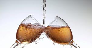 Розовое вино будучи политым в стекла против белой предпосылки, акции видеоматериалы