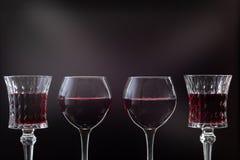 Розовое вино Красное вино в 4 бокалах над темной предпосылкой с лучами света стоковое изображение