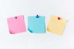 Розовое голубое и желтое бумажное примечание с штырем на листе пены Стоковая Фотография