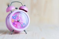 Розовое место будильника на backgrou деревянного стола и древесины Стоковые Фотографии RF