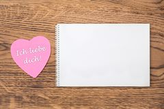 """Розовое сердце пост-оно с текстом """"dich liebe Ich """"и тетрадью на деревянной предпосылке Перевод: """"Я тебя люблю """" стоковое изображение rf"""