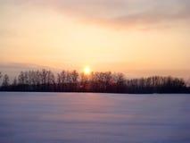 Розовое солнце и голубой снег на заходе солнца Стоковая Фотография