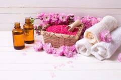 Розовое соль моря в шаре, полотенцах, бутылках с маслами ароматности и штыре Стоковое фото RF