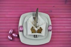 Розовое урегулирование места расписания пасхи в белизне с шоколадом обернуло украшения формы яичек и кролика зайчика Стоковое Фото