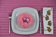 Розовое урегулирование места расписания пасхи в белизне с шоколадом обернуло украшения формы яичек и кролика зайчика Стоковая Фотография