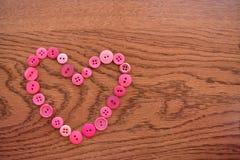 розовое шить сердце кнопки на древесине стоковые фотографии rf