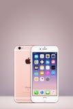 Розовое iPhone 7 Яблока золота с iOS 10 на экране на вертикальной предпосылке градиента с космосом экземпляра Стоковая Фотография