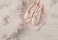 Розовые ботинки и перо pointe балета на белой деревянной предпосылке Стоковое Изображение