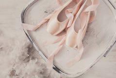 Розовые ботинки и перо pointe балета на белой деревянной предпосылке Стоковая Фотография