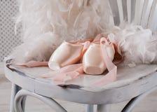 Розовые ботинки и перо pointe балета на белой деревянной предпосылке Стоковое фото RF