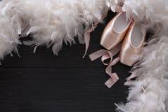 Розовые ботинки и перо pointe балета на черной деревянной предпосылке Стоковое фото RF