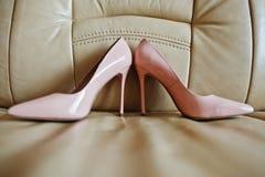 Розовые ботинки невест на высоких пятках на кожаной софе Стоковая Фотография