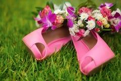 Розовые ботинки с розовым букетом на траве, днем свадьбы Стоковые Изображения