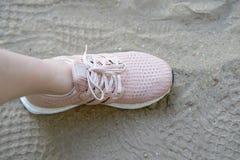 Розовые ботинки runnung один бортовой штемпель на песке с ботинками печатают Стоковые Фотографии RF