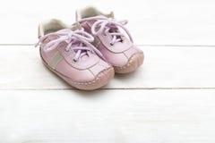 Розовые ботинки ` s девушки маленькие на деревянной предпосылке Стоковые Изображения