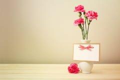 Розовые гвоздики на белой вазе с пустой поздравительной открыткой Стоковые Фотографии RF