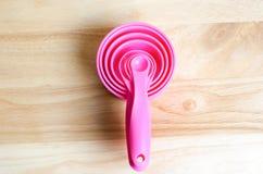 Розовые измеряя ложки в различных размерах на деревянном столе Стоковая Фотография RF