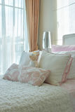 Розовые и бежевые подушки на кровати рядом с окном Стоковые Фото