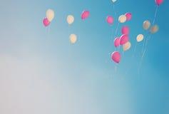 Розовые и белые воздушные шары летая в небо, подкрашиванное фото Стоковые Фотографии RF