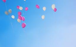 Розовые и белые воздушные шары летая в небо Стоковое Изображение RF