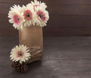 Розовые и белые цветки и тимберс gerbera на деревянной предпосылке с сумкой Стоковая Фотография