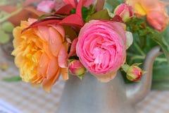 Розовые и желтые розы в чайнике металла на таблице Стоковое фото RF