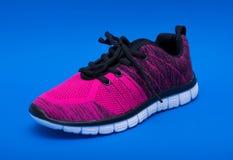 Розовые и черные ботинки женщины спорта изолированные на голубой предпосылке Стоковое фото RF