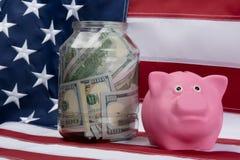 Розовые копилка и деньги в банке на предпосылке флага Стоковое Изображение