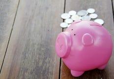 Розовые копилка и монетки на деревянном поле Стоковые Фотографии RF