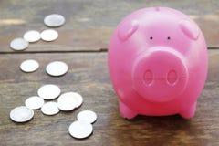 Розовые копилка и монетки на деревянном поле Стоковое Фото