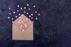 Розовые, красные и белые сердца конфеты сахара помадок летают из конверта бумаги ремесла на темной каменной предпосылке Принципиа Стоковое Изображение RF