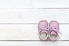 Розовые маленькие ботинки на белой деревянной предпосылке Стоковое фото RF