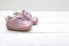 Розовые маленькие ботинки для девушки на белой деревянной предпосылке Стоковые Изображения